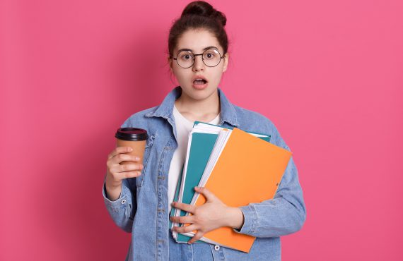 Astonished woman with widely opened mouth, holding takeaway coffee and paper folder, sees something shocked, looks at camera, being late for lectures.